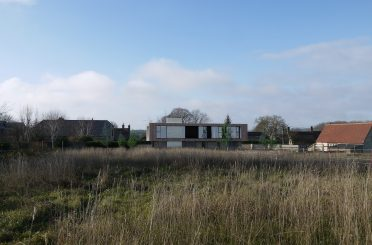 A CGI of the new building in context, with the listed barn (now converted to a house) on the right and the unlisted barn to the left. The council's officer's claimed that the new house would be so harmful to the setting and thus refused, but the members of the planning committee disagreed.